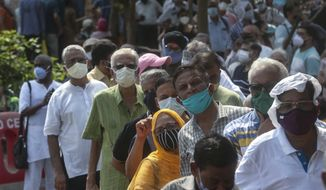 People queue up for COVID-19 vaccine in Mumbai, India, Monday, April 26, 2021. New infections are rising faster in India than any other place in the world, stunning authorities and capsizing its fragile health system. (AP Photo/Rafiq Maqbool)