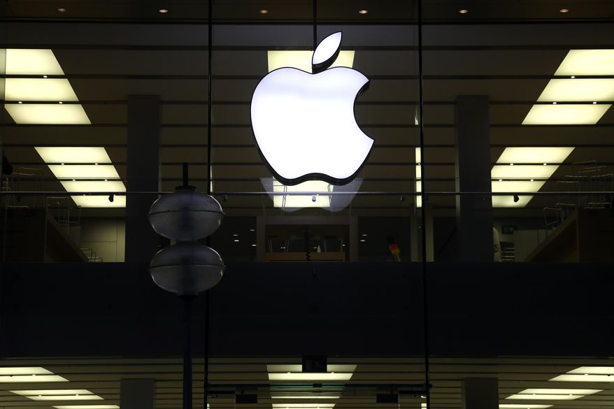 """This Dec. 16, 2020 file photo shows an illuminated Apple logo at a store in Munich, Germany. Apple is following through on its pledge to crack down Facebook and other snoopy apps that secretly shadow people on their iPhones to help sell more advertising. The new privacy feature, dubbed """"App Tracking Transparency,"""" rolled out Monday, April 26, 2021, as part of an update to the operating system powering the iPhone and iPad. (AP Photo/Matthias Schrader, File)"""