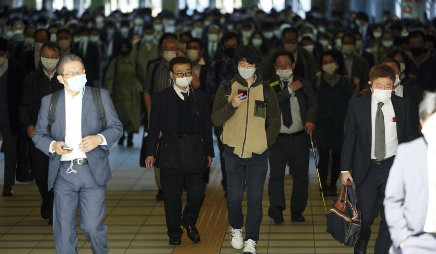A station passageway is crowded with commuters wearing face masks during a rush hour at Shinagawa Station Monday, April 26, 2021, in Tokyo. Japan declared a third state of emergency for Tokyo and three western prefectures from Sunday amid skepticism it will be enough to curb a rapid coronavirus resurgence just three months ahead of the Olympics. (AP Photo/Eugene Hoshiko)