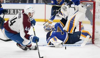 Colorado Avalanche's Kiefer Sherwood (44) is unable to score past St. Louis Blues goaltender Jordan Binnington, right, during the third period of an NHL hockey game Monday, April 26, 2021, in St. Louis. (AP Photo/Jeff Roberson)