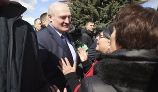 Belarus President Alexander Lukashenko speaks with local residents in the town of Bragin, some 360 km ( 225 miles) south-east of Minsk, Belarus, Monday, April 26, 2021. Alexander Lukashenko took part in a requiem rally on the occasion of the 35th anniversary of the Chernobyl disaster. (Maxim Guchek/BelTA Pool Photo via AP)
