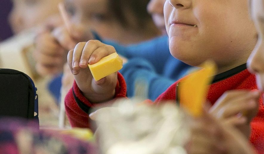 In this Monday, Oct. 29, 2018, file photo, kids eat lunch at an elementary school in Paducah, Ky. The Biden administration is expanding a program to feed as many as 34 million school children during the summer months. They're using funds from the coronavirus relief package approved in March 2021. (Ellen O'Nan/The Paducah Sun via AP, File)