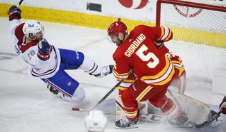 Montreal Canadiens' Jeff Petry, left, falls to the ice after being tripped by Calgary Flames' Mark Giordano during third-period NHL hockey game action in Calgary, Alberta, Monday, April 26, 2021. (Jeff McIntosh/The Canadian Press via AP)
