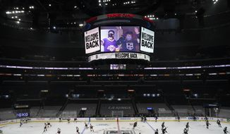 A sign welcomes back fans amid the COVID-19 pandemic as the Los Angeles Kings and Anaheim Ducks warm up before an NHL hockey game Tuesday, April 20, 2021, in Los Angeles. (AP Photo/Marcio Jose Sanchez) **FILE**