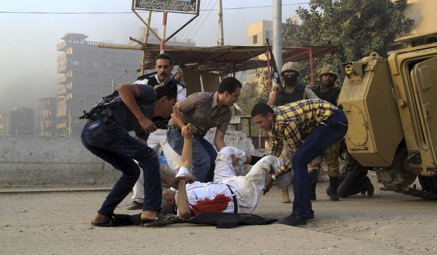 FILE - In this Sept. 19, 2013 file photo, Egyptian security forces lift the lifeless body of Giza Police Gen. Nabil Farrag who was killed after unidentified militants opened fire on security forces deployed in the town of Kerdasa, close to the pyramids at Giza, Egypt. On Monday, April 26, 2021, executed nine men convicted of murder in the attack on a police station in 2013, security officials and a rights lawyer said. The assault resulted in the deaths of 15 people, including 11 police. (AP Photo/Ahmed Ramadan, File)
