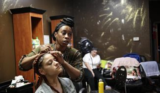 Matilda Kromah, center, braids a clients hair at her salon, Thursday, April 22, 2021, in Brooklyn Center, Minn. The salon was looted after a white police officer fatally shot a Black man this month, and Kromah faced a resurgence of the trauma from the civil war in Liberia she fled over 20 years ago. (AP Photo/Stephen Groves)