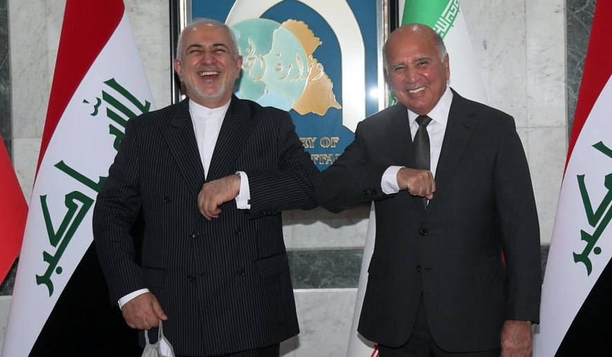 Iraqi Foreign Minister Fouad Hussein, right, meets with visiting Iranian counterpart Mohammad Javad Zarif in Baghdad, Iraq, Monday, April 26, 2021. (AP Photo/Khalid Mohammed)