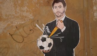 """A mural depicting Juventus president Andrea Agnelli making a hole in a football with a knife, appeared in Rome, Thursday, April 22, 2021. Juventus was one of the three Italian soccer clubs among the founding members of the now defunct project to give life to a """"Super League"""" of European clubs. (AP Photo/Andrew Medichini)"""