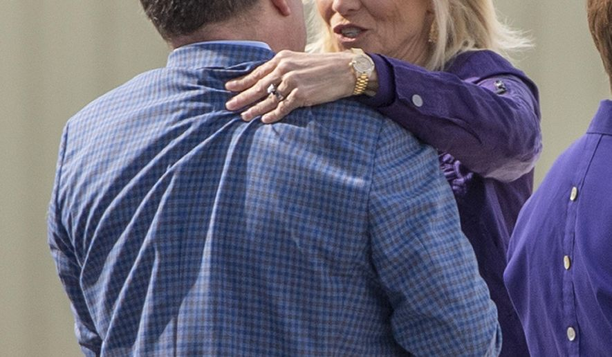 Speaking to Athletics Director Scott Woodward, left, former Baylor women's basketball coach Kim Mulkey arrives at Metro Airport to become LSU's women's basketball coach Monday, April 26, 2021, in Baton Rouge, La. (Bill Feig/The Advocate via AP)