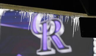 Icicles hang down from the upper deck of Coors Field before a baseball game between the Colorado Rockies and the New York Mets, Saturday, April 17, 2021, in Denver, the day after a spring snow storm. (AP Photo/David Zalubowski)
