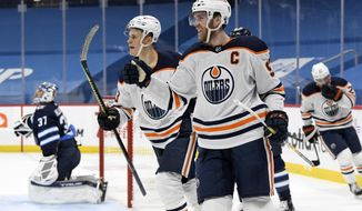 Edmonton Oilers' Connor McDavid (97) celebrates his goal with teammate Jesse Puljujarvi (13) during the first period of an NHL game in Winnipeg, Manitoba, Monday, April 26, 2021. (Fred Greenslade/The Canadian Press via AP)