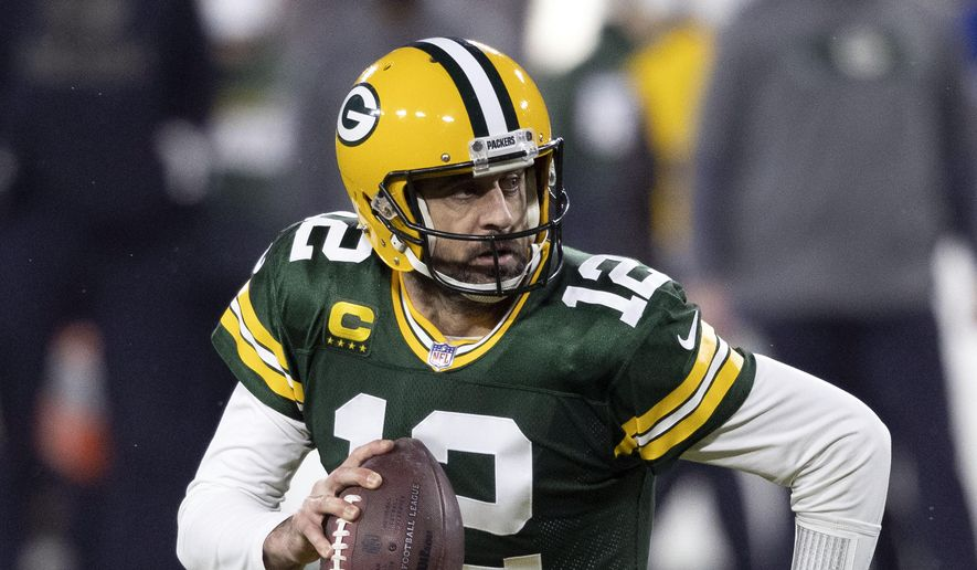 """In this Jan. 16, 2021, file photo, Green Bay Packers quarterback Aaron Rodgers (12) runs during an NFL divisional playoff football game against the Los Angeles Rams in Green Bay, Wis. Packers general manager Brian Gutekunst says the team remains committed to Rodgers """"for the foreseeable future"""" one year after trading up in the first round to draft the three-time MVP's potential successor. (AP Photo/Jeffrey Phelps, File) **FILE**"""