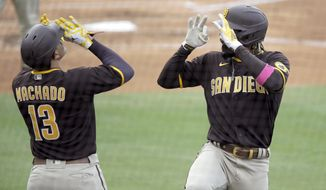 San Diego Padres' Fernando Tatis Jr., right, celebrates his solo home run with Manny Machado during the fourth inning of a baseball game against the Los Angeles Dodgers in Los Angeles, Sunday, April 25, 2021. (AP Photo/Alex Gallardo)
