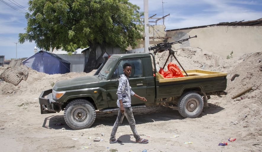 A man walks past a position of military forces supporting anti-government opposition groups in Mogadishu, Somalia Monday, April 26, 2021. Soldiers angry over the president's extended stay in power took up key positions across Somalia's capital on Monday, but there was none of the gunfire that shattered the previous night in Mogadishu. (AP Photo/Farah Abdi Warsameh)