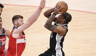 San Antonio Spurs forward DeMar DeRozan, right, goes to the basket against Washington Wizards forward Davis Bertans, left, during the first half of an NBA basketball game, Monday, April 26, 2021, in Washington. (AP Photo/Nick Wass)
