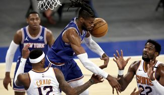 New York Knicks' Reggie Bullock, top center, fights for a rebound with Phoenix Suns' Torrey Craig (12) and Deandre Ayton (22)  in the third quarter of an NBA basketball game Monday, April 26, 2021, in New York. (Elsa/Pool Photo via AP)