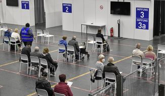 People wait at the vaccination center in Gelsenkirchen, Germany, Monday, April 26, 2021. Germany's COVID-19 vaccination program will be discussed at a meeting with Germany's state Governors and Chancellor Angela Merkel in Berlin today. (AP Photo/Martin Meissner)