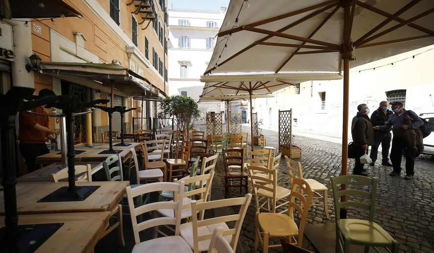 Chairs and tables are being prepared outside a restaurant ahead of Monday's reopening following the ease of COVID-19 restrictions, in Rome, Friday, April 23, 2021. Even Italy's tentative reopening is satisfying no one. Outdoor dining is too little, too late for restaurant owners whose survival is threatened by a year of rotating closures. Yet the nation's weary virologists worry that Monday, April 26, 2021, will see people crowding bars and restaurants and bring yet another spike to the virus that has not really properly receded yet. (Cecilia Fabiano/LaPresse via AP)