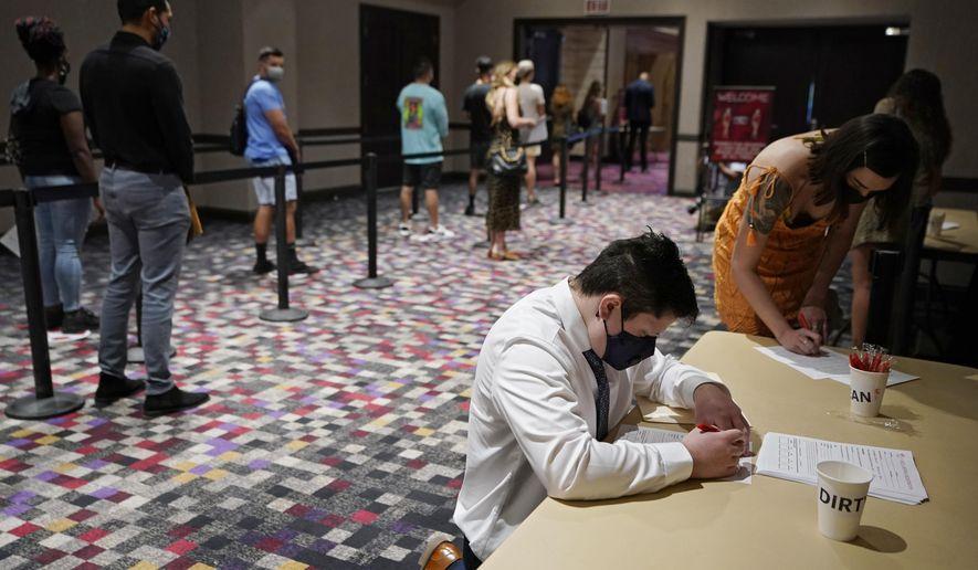 In this April 22, 2021, file photo, people wait in line to apply for seasonal jobs at Virgin Hotels Las Vegas in Las Vegas. (AP Photo/John Locher, File)