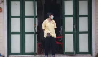A shop assistant wearing a face mask to help curb the spread of the coronavirus stands in front of her shop in Khao San road, a popular hangout for Thais and tourists in Bangkok, Thailand, Monday, April 26, 2021. Cinemas, parks and gyms were among venues closed in Bangkok as Thailand sees its worst surge of the pandemic. A shortage of hospital beds, along with a failure to secure adequate coronavirus vaccine supplies, have pushed the government into imposing the new restrictions.  (AP Photo/Anuthep Cheysakron)