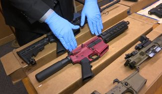 """In this file photo taken Wednesday, Nov. 27, 2019, is Sgt. Matthew Elseth with """"ghost guns"""" on display at the headquarters of the San Francisco Police Department in San Francisco. (AP Photo/Haven Daley, File)"""
