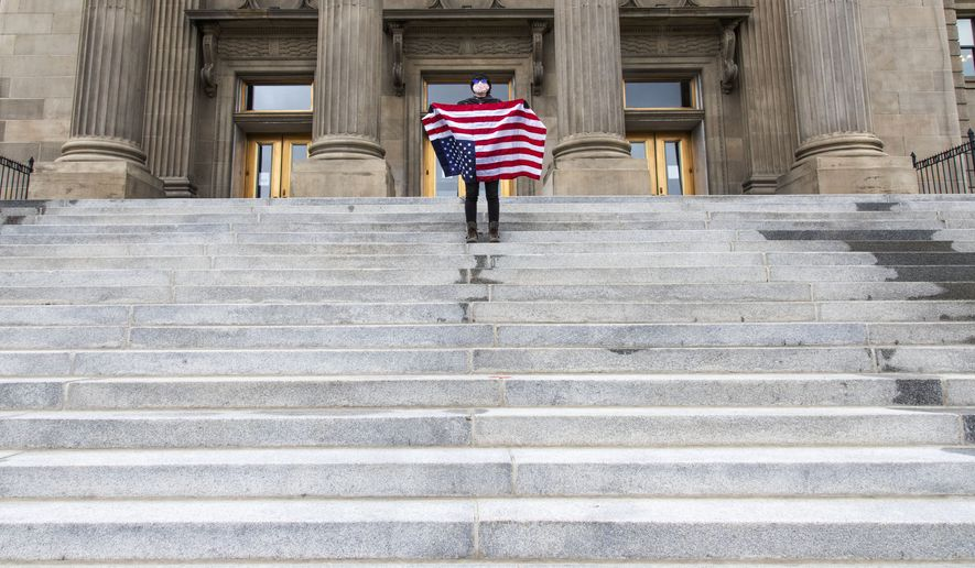 """A student holding a U.S. flag upside down stands atop the steps at the Idaho Capitol Building Monday, April 26, 2021, in downtown Boise. The Idaho Senate has approved legislation aimed at preventing schools and universities from """"indoctrinating"""" students through teaching critical race theory, which examines the ways in which race and racism influence American politics, culture and the law. (Darin Oswald/Idaho Statesman via AP) **FILE**"""