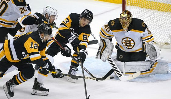 Pittsburgh Penguins' Zach Aston-Reese (12) gets off a shot in front of Boston Bruins goaltender Tuukka Rask (40) with Jeremy Lauzon (55) defending during the first period of an NHL hockey game in Pittsburgh, Tuesday, April 27, 2021.(AP Photo/Gene J. Puskar)