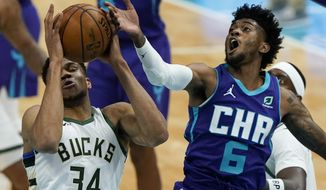 Milwaukee Bucks forward Giannis Antetokounmpo, left, blocks a shot by Charlotte Hornets forward Jalen McDaniels during the first half of an NBA basketball game on Tuesday, April 27, 2021, in Charlotte, N.C. (AP Photo/Chris Carlson)