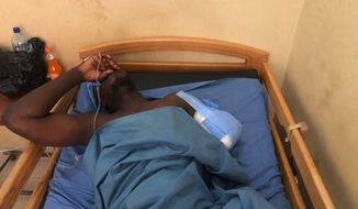A soldier wounded in an attack lays in a bed in a military hospital in Burkina Faso's capital Ouagadougou Tuesday April 27, 2021. Three foreigners and one soldier are missing in Burkina Faso after being attacked in an ambush by gunmen during an anti-poaching patrol near a national park in the country's east near Pama town according to security and government officials. (AP Photo/Sam Mednick)