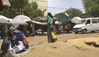 A woman walks past a central market in N'Djamena, Chad, Sunday, April 25, 2021.  (AP Photo/Sunday Alamba)