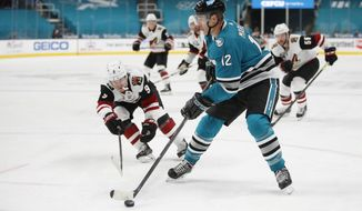 Arizona Coyotes right wing Clayton Keller (9) fights for the puck against the San Jose Sharks center Patrick Marleau (12) during the third period of an NHL hockey game in San Jose, Calif., Monday, April 26, 2021. (AP Photo/Josie Lepe)