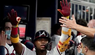 Atlanta Braves' Ronald Acuna Jr. celebrates in the dugout after hitting a home run during the fifth inning of the team's baseball game against the Chicago Cubs on Tuesday, April 27, 2021, in Atlanta. (AP Photo/John Bazemore)