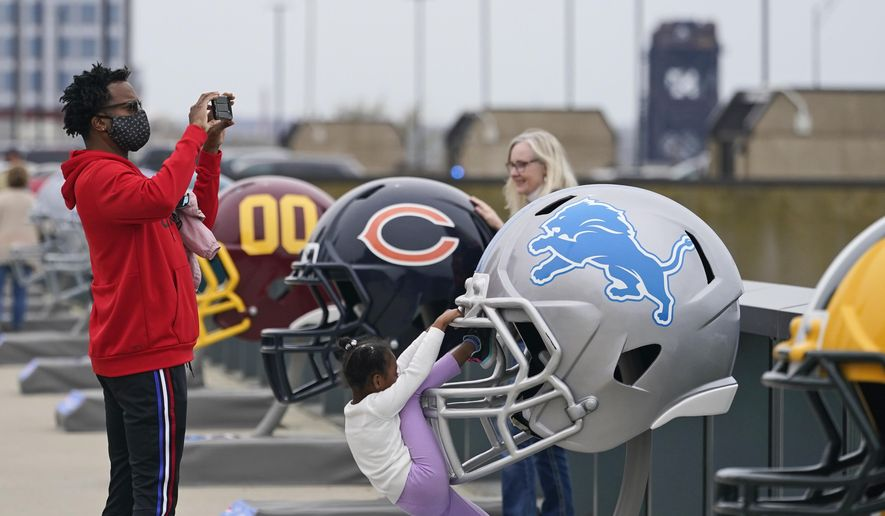 A man takes a picture where 32 teams' helmets are displayed, Saturday, April 24, 2021, in Cleveland, where the NFL Draft will be held April 29-May 1. (AP Photo/Tony Dejak)