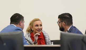 Florida Senators Travis Hutson, left, Lauren Book, center, and Manny Diaz Jr., talk during a senate committee meeting, Tuesday, April 27, 2021, at the Capitol in Tallahassee, Fla. (AP Photo/Wilfredo Lee)