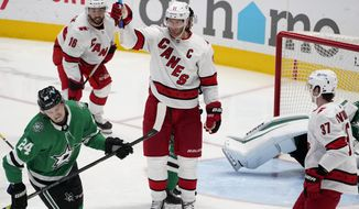 Dallas Stars left wing Roope Hintz (24) skates away as Carolina Hurricanes' Jordan Staal (11) celebrates scoring in the second period of an NHL hockey game in Dallas, Tuesday, April 27, 2021. The Hurricanes' Vincent Trocheck (16) and Andrei Svechnikov (37) skate to join the celebration. (AP Photo/Tony Gutierrez)