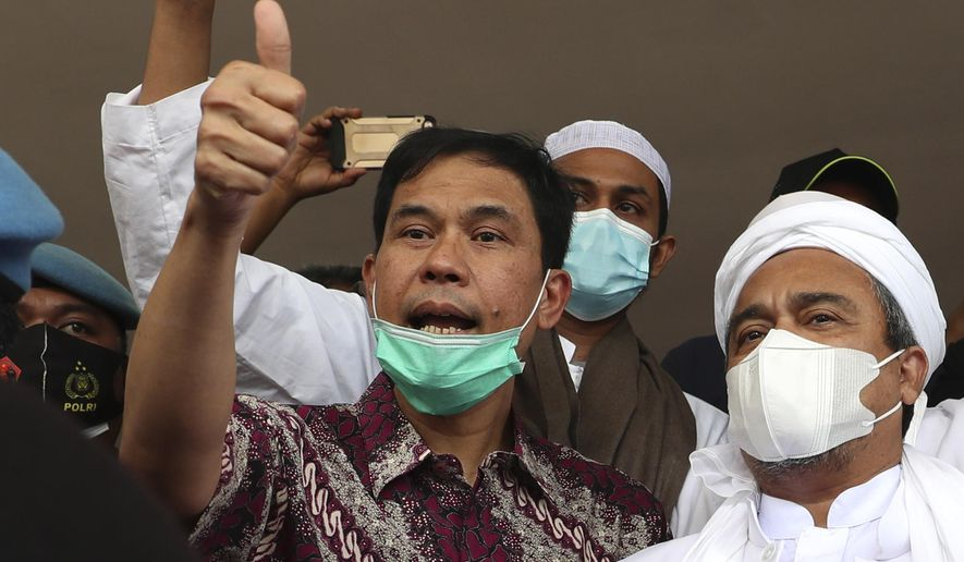 FILE - In this Saturday Dec. 12, 2020 file photo, general secretary of the now-defunct Islam Defenders Front Munarman, left, who is also the lawyer of firebrand cleric Rizieq Shihab, right, gestures at reporters after Rizieq's questioning at the Regional Police Headquarters in Jakarta, Indonesia. Members of Indonesia's counterterrorism police squad on Tuesday April 27, 2021, arrested Munarman who was accused of inciting people to terrorism acts and pledged allegiance to the Islamic State group, police said. (AP Photo/Achmad Ibrahim, File)
