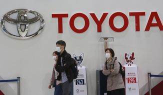 FILE - In this Nov. 2, 2020, file photo, visitors walk at a Toyota showroom in Tokyo. Toyota Motor Corp. has acquired the self-driving division of American ride-hailing company Lyft for $500 million, in a move that underlines the Japanese automaker's ambitions in that technology, announced Tuesday, April 27, 2021. (AP Photo/Koji Sasahara, File)