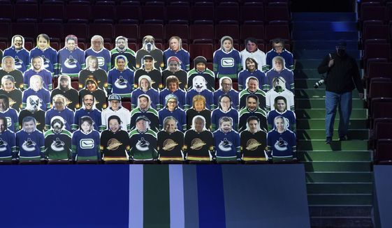 Cardboard cutouts of fans are displayed in the seats before an NHL hockey game between the Vancouver Canucks and the Toronto Maple Leafs in Vancouver, British Columbia, Sunday, April 18, 2021. (Darryl Dyck/The Canadian Press via AP) **FILE**