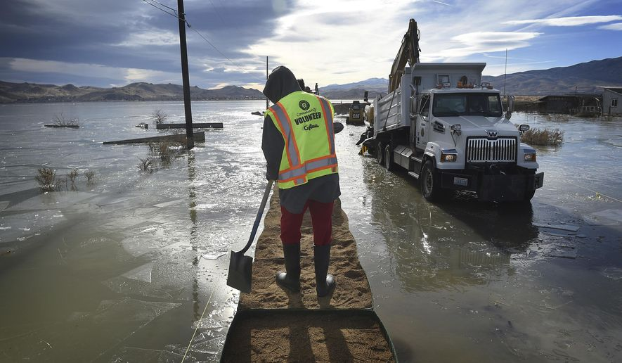 FILE - In this Dec. 19, 2017, file photo, Washoe County sets up some HESCO barriers on the edge of Swan Lake floodwaters in Lemmon Valley, north of Reno, Nev. Reno city officials say they've reached a tentative agreement to pay $4.5 million to settle a lawsuit brought by residents whose Lemmon Valley homes were flooded north of town in 2017 after the city diverted excess storm water into a local lake basin. The city council is expected to approve the payment on May 12, 2021, which would resolve all existing state and federal lawsuits, the Reno Gazette Journal reported. (Jason Bean/The Reno Gazette-Journal via AP, File)