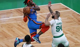 Oklahoma City Thunder forward Luguentz Dort, left, drives to the basket against Boston Celtics guard Evan Fournier, right, during the first half of an NBA basketball game, Tuesday, April 27, 2021, in Boston. (AP Photo/Charles Krupa)