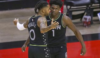 Minnesota Timberwolves guard D'Angelo Russell (0) and forward Anthony Edwards (1) celebrate the team's win over the Houston Rockets in an NBA basketball game Tuesday, April 27, 2021, in Houston. (Thomas Shea/Pool Photo via AP)