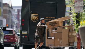 A UPS driver delivers packages in Philadelphia, Monday, April 26, 2021. A surge in the volume of deliveries that arrived with the start of the pandemic has not eased at UPS, where consolidated average daily volume jumped 14.3% in the first quarter. The Atlanta company on Tuesday, April 27 posted earnings of $4.79 billion, or $5.47 per share. (AP Photo/Matt Rourke)