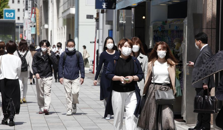 People wearing face masks to protect against the spread of the coronavirus walk on a street in Tokyo, Tuesday, April 27, 2021. Japan declared a state of emergency from Sunday to curb a rapid coronavirus resurgence, the third since the pandemic began. (AP Photo/Koji Sasahara)