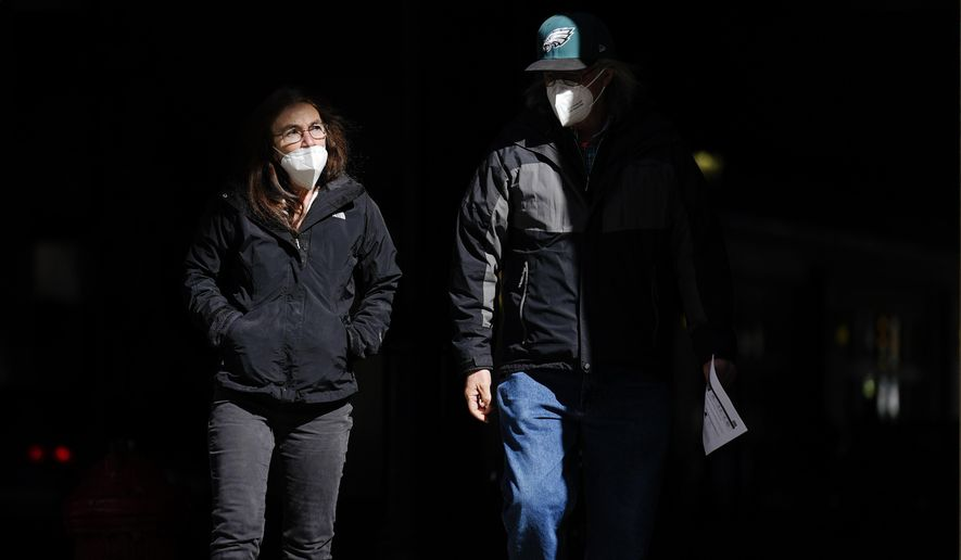 FILE - In this Wednesday, March 3, 2021 file photo, people wearing face masks as a precaution against the coronavirus walk through a shaft of light on a street in Philadelphia. On Tuesday, April 27, 2021, U.S. health officials say fully vaccinated Americans don't need to wear masks outdoors anymore unless they are in a big crowd of strangers, and those who are unvaccinated can go without a face covering outside in some cases, too. (AP Photo/Matt Rourke)