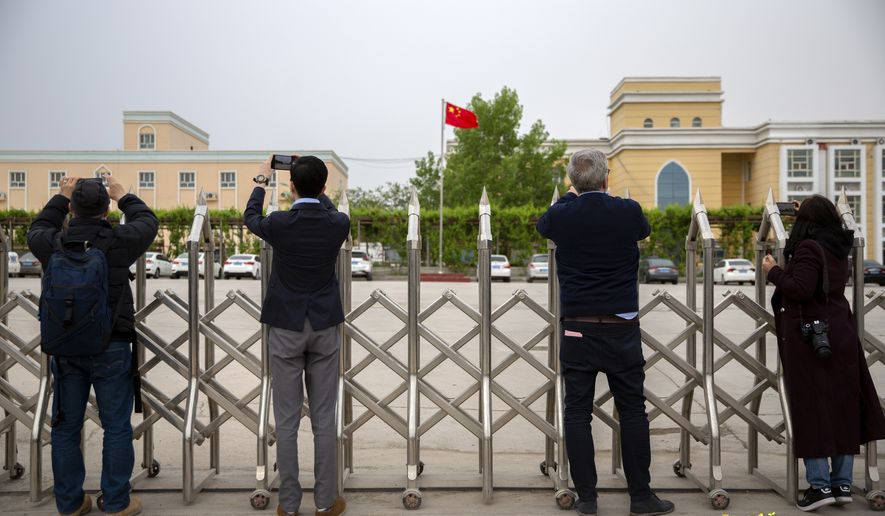 Journalists and government officials take photos outside a location that was identified in early 2020 as a re-education facility by an Australian think tank, which the Chinese government asserts is currently home to a veterans' affairs bureau and other offices, in Turpan in western China's Xinjiang Uyghur Autonomous Region during a government organized trip for foreign journalists, Thursday, April 22, 2021. (AP Photo/Mark Schiefelbein)
