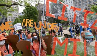 Annika Iwugo, 16, of Takoma Park, Md., center, helps to hold a banner as she joins fellow supporters of immigration reform in protesting for a path to citizenship and an end to detentions and deportations, Wednesday, April 28, 2021, in Washington. (AP Photo/Jacquelyn Martin) ** FILE **