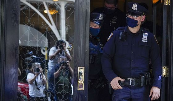 Members of the media are reflected in the widow a door as New York City Police officers walk out of the apartment building where former New York Mayor Rudy Giuliani resides, Wednesday, April 28, 2021, in New York. Federal agents on Wednesday raided Giulianis Manhattan home and office, seizing computers and cell phones in a major escalation of the Justice Departments investigation into the business dealings of former President Donald Trumps personal lawyer. (AP Photo/Mary Altaffer)