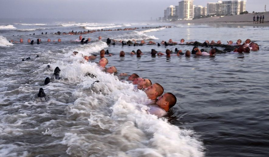 """This May 4, 2020, photo provided by the U.S. Navy shows SEAL candidates participating in """"surf immersion"""" during Basic Underwater Demolition/SEAL (BUD/S) training at the Naval Special Warfare (NSW) Center in Coronado, Calif. U.S. Navy SEALs are undergoing a major transition to improve leadership and expand their commando capabilities. (MC1 Anthony Walker/U.S. Navy via AP)"""