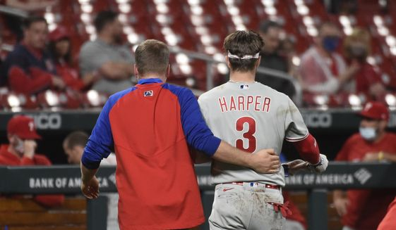 Philadelphia Phillies right fielder Bryce Harper, right, is helped off the field after getting hit by a pitch during the sixth inning of the team's baseball game against the St. Louis Cardinals on Wednesday, April 28, 2021, in St. Louis. (AP Photo/Joe Puetz)
