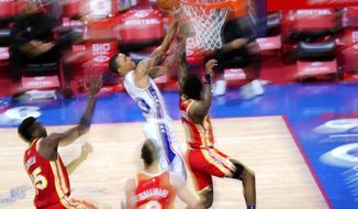 Philadelphia 76ers' George Hill, center, goes up for a shot against Atlanta Hawks' Brandon Goodwin, from right, Danilo Gallinari and Clint Capela during the second half of an NBA basketball game, Wednesday, April 28, 2021, in Philadelphia. (AP Photo/Matt Slocum)